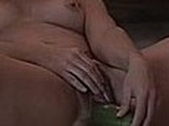 Girl laying on the ground and stuffing her hairy pussy with a big cucumber, she can't stop smiling too, she just loves making amateur masturbation videos.